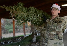 U.S. Army Spc. Michael Moncada, 567th Inland Cargo Transfer Company, 53rd Transportation Battalion, 7th Transportation Brigade (Expeditionary) cargo specialist, carries a live Christmas tree during the Christmas SPIRIT Foundation's Trees for Troops program at Joint Base Langley-Eustis, Va., Dec. 1, 2017.