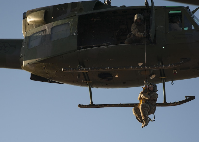 U.S. Air Force Chief Master Sgt. Juliet Gudgel, command chief master sergeant of Air Education and Training Command, is lifted into a UH-1H Huey during a rescue training scenario at Kirtland Air Force Base, N.M., Nov. 27, 2017. On her second day of the visit, Gudgel was able to participate in four training missions with the Airmen of the 58th SOW. (U.S. Air Force photo by Staff Sgt. J.D. Strong II)