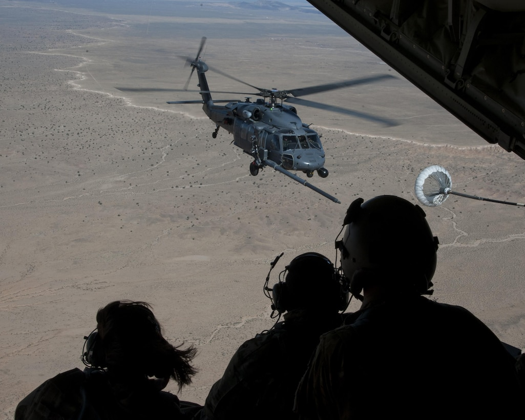 U.S. Air Force Chief Master Sgt. Juliet Gudgel, command chief master sergeant of Air Education and Training Command, watches an HH-60 Pave Hawk refueling training mission at Kirtland Air Force Base, N.M., Nov. 27, 2017. The chief went on four separate flights back-to-back in the course of six hours witnessing a refueling and drop mission in a C-130J, an aerial gunner training in an HH-60 Pave Hawk, hoist training in a CV-22 Osprey and a rescue hoist mission in UH-1H Huey. (U.S. Air Force photo by Staff Sgt. J.D. Strong II)