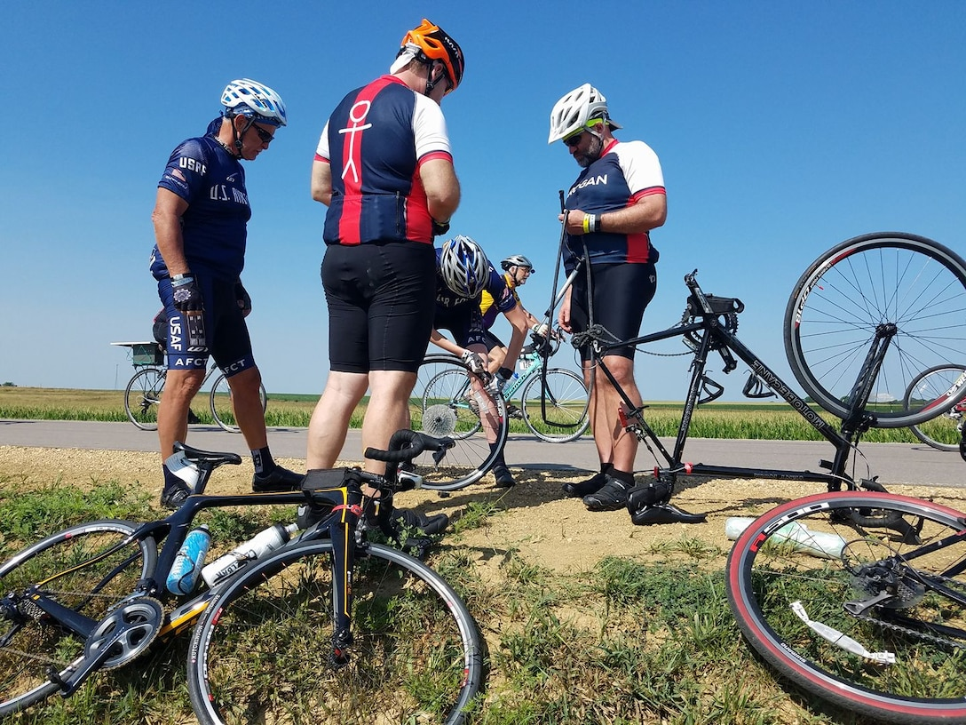 Members of the Air Force Cycling Team help change a flat tire during the Register's Annual Great Bike Ride Across Iowa near Spencer, Iowa, July 24. The AFCT works to promote the Air Force by interacting with the American public at cycling events across the United States. (Courtesy Photo)