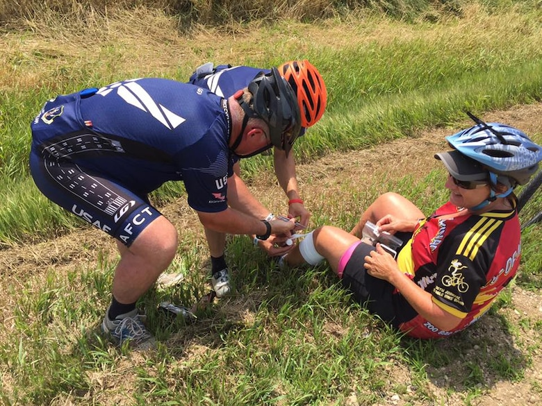 Members of the Air Force Cycling Team help an injured cyclist after she fell during the Register's Annual Great Bike Ride Across Iowa, in Charles City, Iowa, July 27, 2017. During the RAGBRAI, AFCT members provided assistance to more than 5,000 cyclists. The team works to promote the Air Force by interacting with the American public at cycling events across the United States. (Courtesy Photo)
