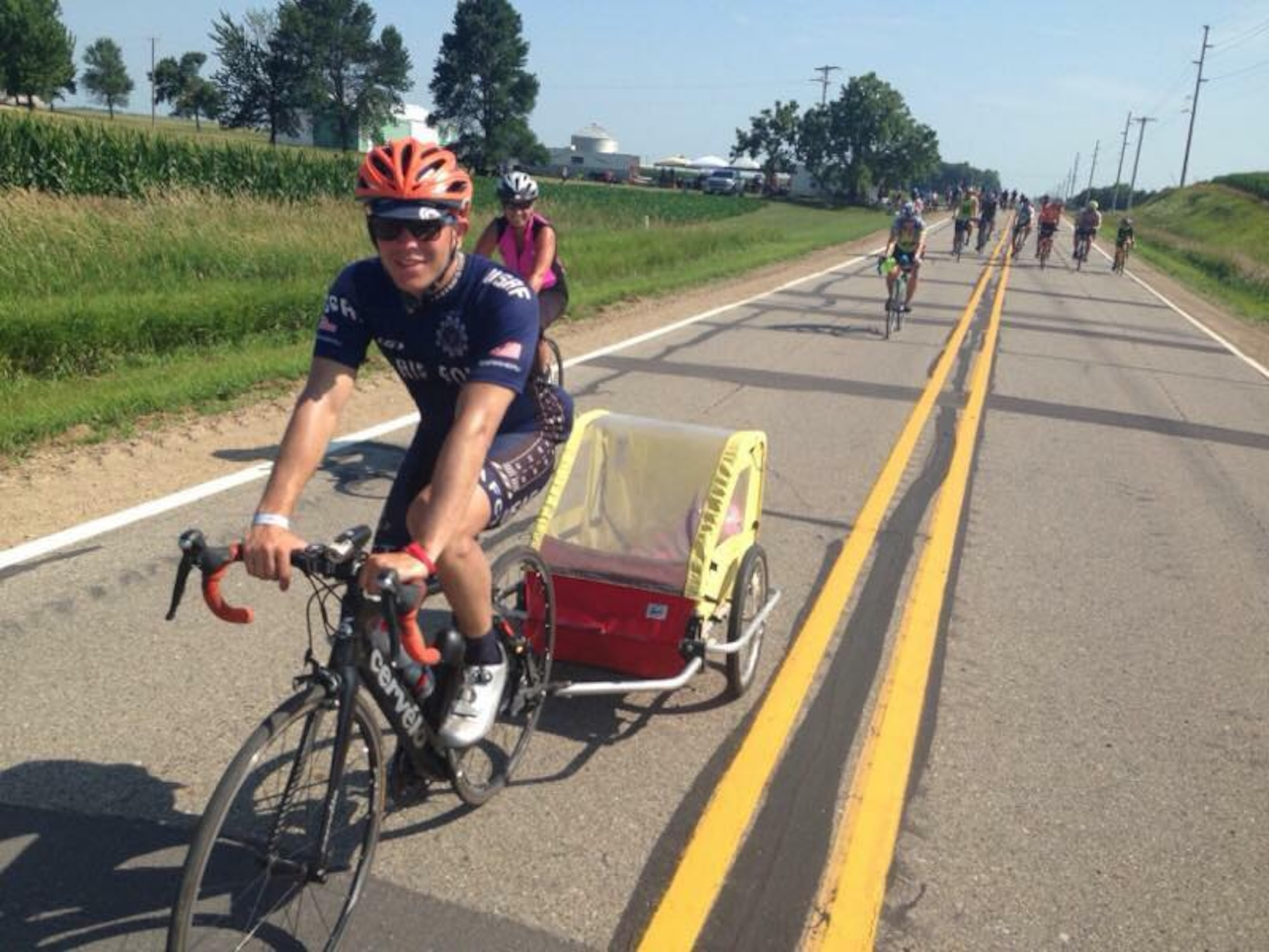 Senior Airman Jacob Pinkney, 860th Aircraft Maintenance Squadron C-17 Globemaster III crew chief and a member of the Air Force Cycling Team, pulls a toddler in a stroller carrier to give the child's mother a break during the Register's Annual Great Bike Ride Across Iowa July 26, 2017. During the RAGBRAI, AFCT members provided assistance to more than 5,000 cyclists. The team works to promote the Air Force by interacting with the American public at cycling events across the United States. (Courtesy Photo)