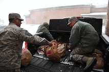 From left to right, Master Sgts. Kepler Baksh, Daniel Cable and Scott Harris load a truck with bags of cookies to deliver to Airmen in the dorms for the annual cookie drive on Grand Forks Air Force Base, N.D., Dec. 4, 2017. Baksh, Cable and Harris were joined by fellow first sergeants volunteers to hand-deliver plates of cookies to their Airmen in the dorms during the holidays. (U.S. Air Force photo by Elora J. Martinez)