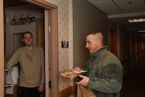 Master Sgt. Scott Harris, first sergeant with the 319th Logistics Readiness Squadron, right, delivers a plate of cookies to Airman 1st Class Austin Erickson, lodging assistant with the 319th Force Support Squadron, during the annual cookie drive on Grand Forks Air Force Base, N.D., on Dec. 4, 2017. Erickson is one of the hundreds of Airmen living in the dorms who each received a plate of treats donated by members of the Spouses Club on base and the local community. (U.S. Air Force photo by Elora J. Martinez)