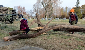 Anna Myers, age three, and Finnigan Myers, age six, children of U.S. Army Lt. Col. Vince Myers, McDonald Army Health Center commander, use a log as a seesaw during a restoration project at Pleasant Shade Cemetery in Hampton, Va. Dec. 2, 2017.