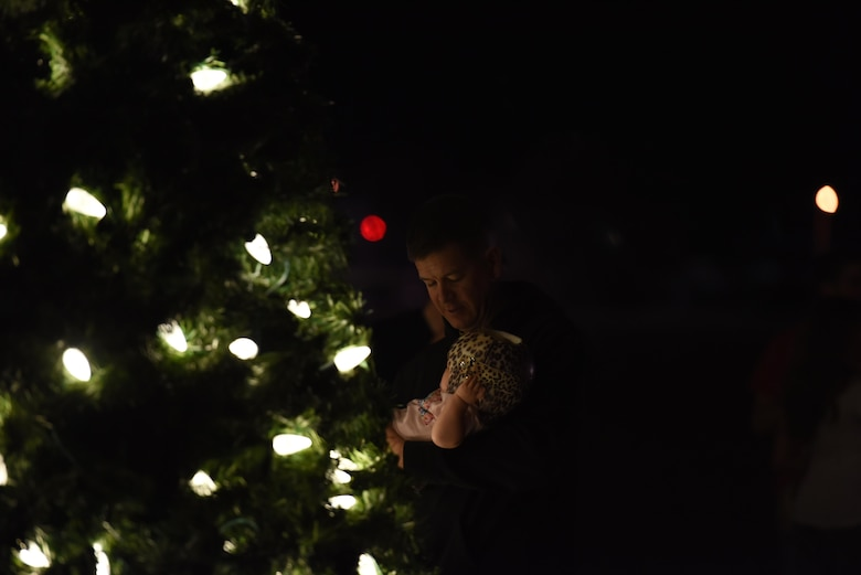 U.S. Marine Corp. Maj. Andrew Armstrong, Marine Corp. Detachment commanding officer, holds a baby during the Tree Lighting Ceremony at the Parade Field on Goodfellow Air Force Base, Texas, Dec. 4, 2017. The event held activities for children such as making decorations or cookies as well as Olaf from the Disney movie Frozen, U.S. Air Force Col. Jeffrey Sorrell, 17th Training Wing vice commander, and Santa Claus. (U.S. Air Force photo by Airman 1st Class Zachary Chapman/ Released)