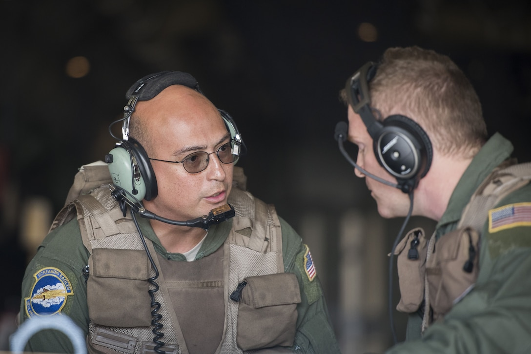 Tech Sgt. Gary Woolridge, 40th Airlift Squadron C-130J Super Hercules loadmaster, talks to Staff Sgt. Craig Morrison, 40 AS C-130J loadmaster, while unloading cargo in preparation for exercise Vigilant Ace 18, Dec. 1, 2017, at Gwangju Airbase, Republic of Korea.