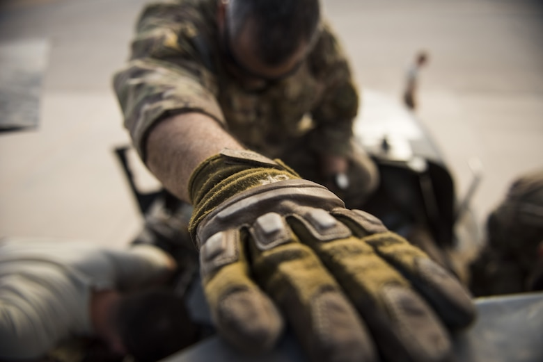 Maintainers assigned to the 801st Expeditionary Maintenance Squadron work together on HH-60G Pave Hawk helicopter engine components November 22, 2017, in an undisclosed location. Maintenance professionals of the 801st EMXS must keep as many aircraft as possible prepared to fly in less that 30 minutes. (U.S. Air Force photo by Staff Sgt. Joshua Kleinholz)
