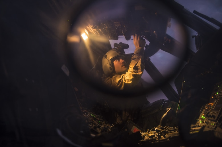 A pilot assigned to the 46th Expeditionary Rescue Squadron checks avionics