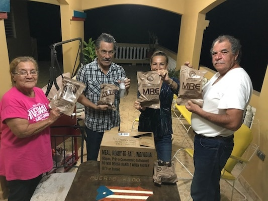 Family, facing viewer, holding MREs