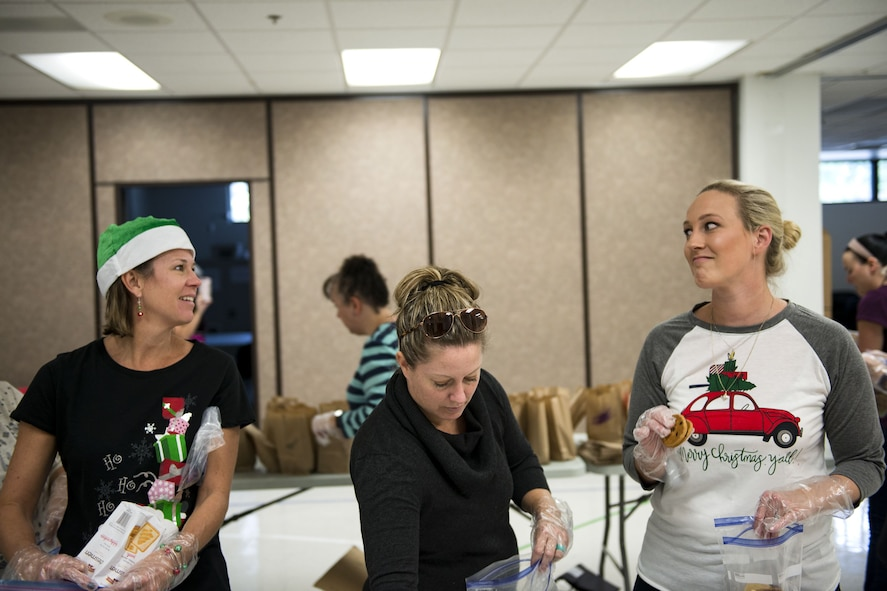 Marcie Chastain, left, Rena Hall, and Elaine McPherson, Team Moody military spouses, pack cookies into bags during the Annual Moody Airmen Cookie Drive, Dec. 4, 2017, at Moody Air Force Base, Ga. Local organizations, Airmen and spouses donated more than 8,000 cookies to approximately 700 dorm residents to show appreciation for the Airmen during the holidays. (U.S. Air Force photo by Airman 1st Class Erick Requadt)