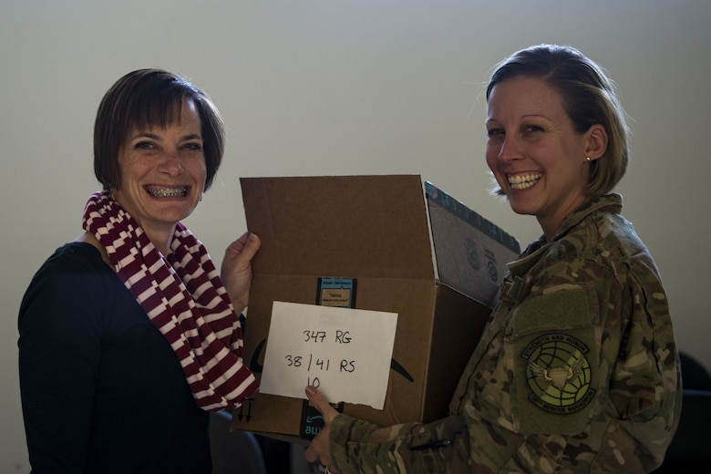 Stacey Gingrich, left, spouse of Col. Jason Gingrich, 347th Rescue Group commander, and Master Sgt. Stephanie Ruepp, 38th Rescue Squadron unit training manager, pose for a photo during the Annual Moody Airmen Cookie Drive, Dec. 4, 2017, at Moody Air Force Base, Ga. Local organizations, Airmen and spouses donated more than 8,000 cookies to approximately 700 dorm residents to show appreciation for the Airmen during the holidays. (U.S. Air Force photo by Airman 1st Class Erick Requadt)