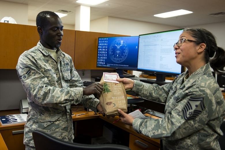 Senior Master Sgt. Regina Dockens, right, 23d Communications Squadron first sergeant, gives a bag of cookies to Airman 1st Class Theophilus Agyare, 23d Contracting Squadron contracting specialist, during the Annual Moody Airmen Cookie Drive, Dec. 5, 2017, at Moody Air Force Base, Ga. Local organizations, Airmen and spouses donated more than 8,000 cookies to approximately 700 dorm residents to show appreciation for the Airmen during the holidays. (U.S. Air Force photo by Airman 1st Class Erick Requadt)