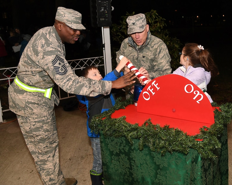 (Left to right) Chief Master Sgt. Henry L. Hayes, Hanscom's command chief, Hunter Kircher, Col. Roman L. Hund, installation commander, and Alexandria Kircher flip the switch to light Hanscom's Christmas tree outside the base chapel Dec. 5.