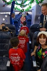 Children from Luke Air Force Base board a holiday-themed plane during the United Fantasy Flight at the Phoenix Sky Harbor International Airport in Phoenix Ariz., Dec. 1, 2017. The flight landed at a nearby hangar that had been transformed into the North Pole. (U.S. Air Force photo/Senior Airman Devante Williams)
