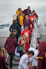 Arizona State University student volunteers meet children as they get off a plane during the United Fantasy Flight at the Phoenix Sky Harbor International Airport in Phoenix Ariz., Dec. 1, 2017.  Several Team Luke children boarded a designated flight and depart to a simulated North Pole which included festive activities, games, holiday treats and a visit from Santa Claus. (U.S. Air Force photo/Senior Airman Devante Williams)
