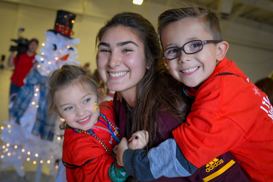 Aria Hueso, Arizona State University water polo athlete, poses with Team Luke children, during the United Fantasy Flight at the Phoenix Sky Harbor International Airport in Phoenix Ariz., Dec. 1, 2017. United Airlines invited children from Luke whose parents are currently deployed to attend the special event. (U.S. Air Force photo/Senior Airman Devante Williams)