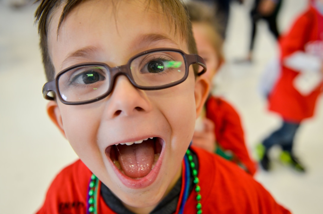 A Team Luke child smiles during the United Fantasy Flight at the Phoenix Sky Harbor International Airport in Phoenix Ariz., Dec. 1, 2017. Several children from Luke, who have a family member currently deployed, were invited to the special event where they received shoes, sweatshirts, blankets, toys, books and a tablet. (U.S. Air Force photo/Senior Airman Devante Williams)