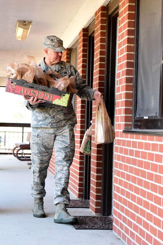 Master Sgt. Doug Harriman, 4th Civil Engineer Squadron first sergeant, delivers packets of cookies during the annual Officer and Civilian Spouses Club Airmen Cookie Drive Dec. 4, 2017, at Seymour Johnson Air Force Base, North Carolina.