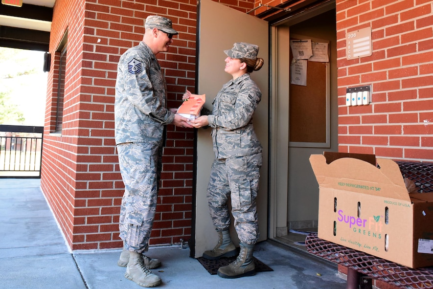 Master Sgt. Christopher Tamble, 4th Medical Group first sergeant, left, hands Airman 1st Class Emily Harnois, 4th Component Maintenance Squadron hydraulics technician, a holiday cookie packet during the annual Officer and Civilian Spouses Club Airmen Cookie Drive Dec. 4, 2017, at Seymour Johnson Air Force Base, North Carolina.