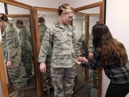 Stacey Butler (right) a clothing designer with the Air Force Life Cycle Management Center's Air Force Uniform Office, measures Capt. Taylor Harrison's maternity Airman Battle Uniform. The new uniforms were designed and developed by the office and are available to pregnant Airmen around the world. ( U.S. Air Force photo / Brian Brackens)