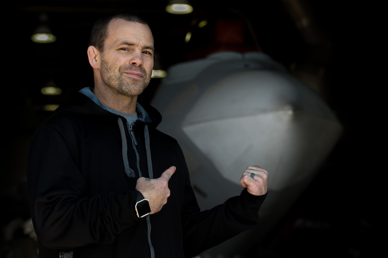 Jens Pulver, former Ultimate Fighting Championship lightweight fighter champion, poses in front of a U.S. Air Force F-22 Raptor during the Mixed Martial Arts Legends Tour at Joint Base Langley-Eustis, Va., Dec. 1, 2017.