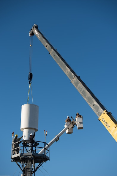 Airmen and contractors guide Offutt Air Force Base's (AFB) legacy Tactical Air Navigation System (TACAN) as a crane operator hoists the system off its tower at Offutt AFB, Nebraska, Nov. 29, 2017.