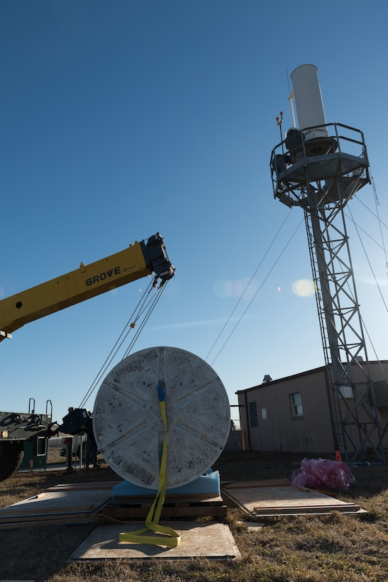 Airmen and contractors install Offutt Air Force Base's (AFB) new Tactical Air Navigation System, background, at Offutt AFB, Nebraska, Nov. 29, 2017.