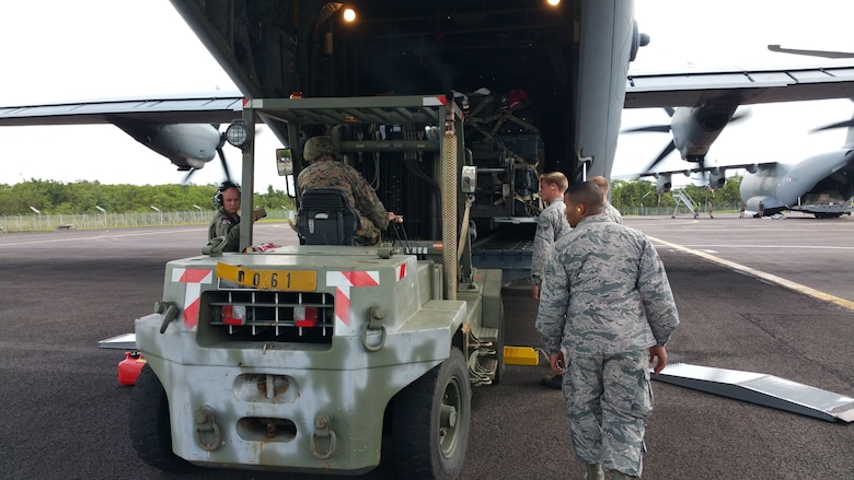 Airmen assigned to the 62nd Aerial Port Squadron load cargo alongside sister service members, Oct. 9, 2017 on the island of Martinique.