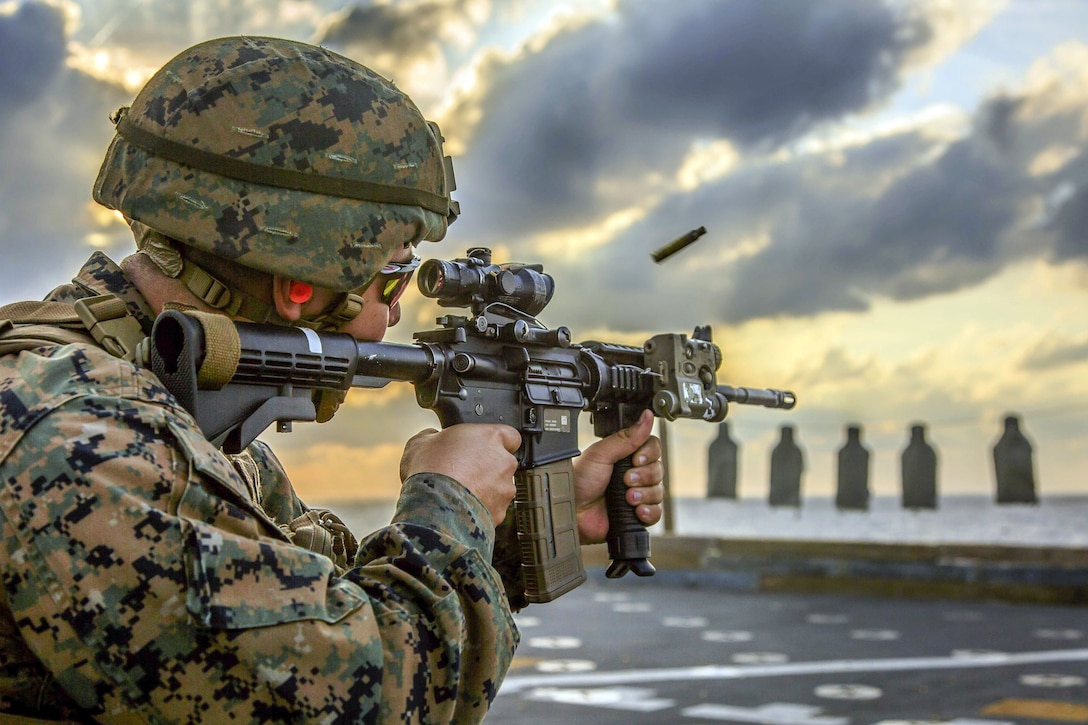 A Marine fires a carbine toward a hanging row of targets on a ship's flight deck.