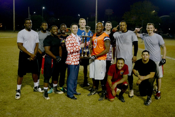 Members of the U.S. Air Forces Central (AFCENT) flag football team surround their trophy at Shaw Air Force Base, S.C. Dec.1, 2017.