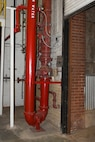 Red-painted fire-suppression pipes are shown near an opened vertical roll-up door in Bldg. 3001 on Nov. 17, 2017, Tinker Air Force Base, Oklahoma. Areas like this have a higher potential for proximity freezing if not monitored closely and doors aren't closed to keep the heat in during below-freezing periods.