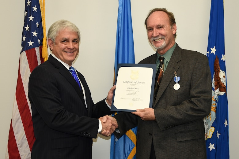 Eberhard Bauer, right, 72nd Air Base Wing Plans and Program Office management analyst is recognized for 20 years of civilian service along with a Civilian Personnel Achievement Award for his contributions on the Civilian Mentoring Council from Robert Sandlin, 72nd ABW director of staff, Nov. 28, 2017, Tinker Air Force Base, Oklahoma. The ceremony took place at the 72nd ABW Headquarters building.