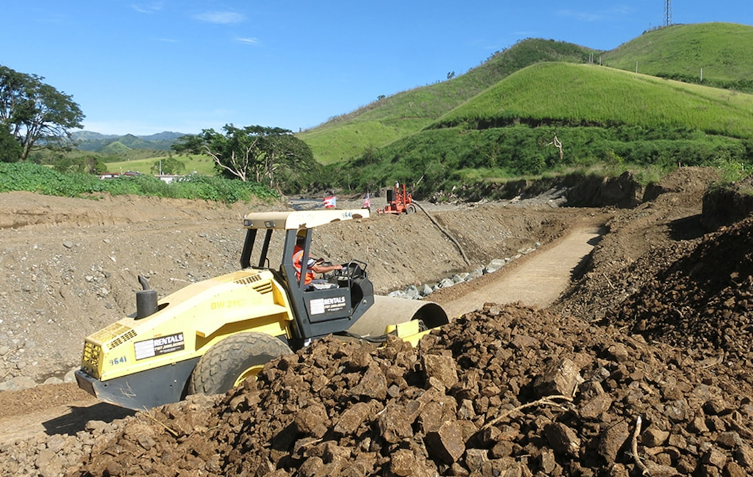 A vibratory soil compactor helps prepare the base of a new levee being constructed in Yauco, Puerto Rico, following Hurricane Maria floods that destroyed the previous one.