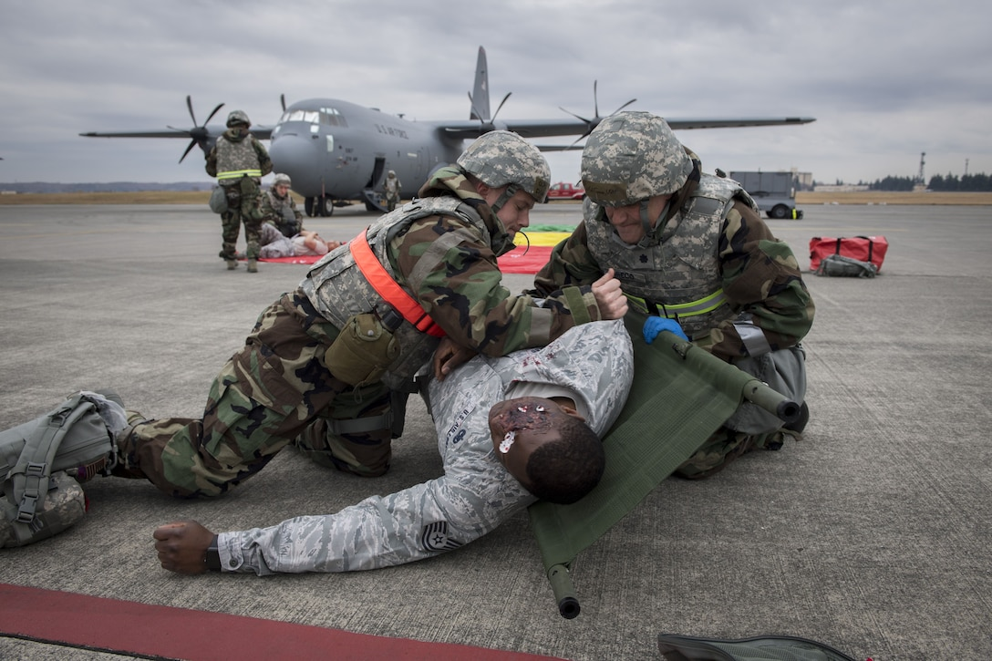 A 374th Medical Squadron medic and on scene doctor work together to place a simulated victim on a stretcher during exercise Beverly Morning 17-08 in conjunction with exercise Vigilant Ace 18, Dec. 4, 2017, at Yokota Air Base, Japan.