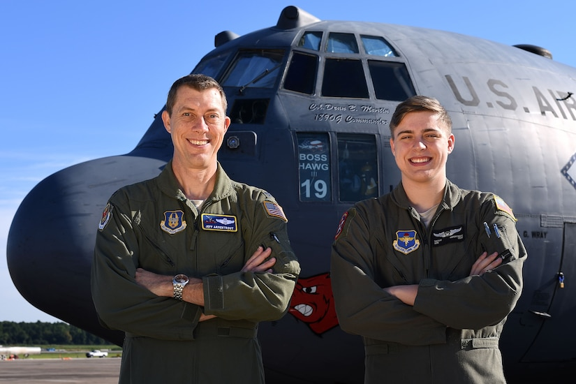 Airmen father and son stand next to each other in front of a c-130 military aircraft.