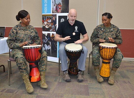 Two Marines play drums with a man.