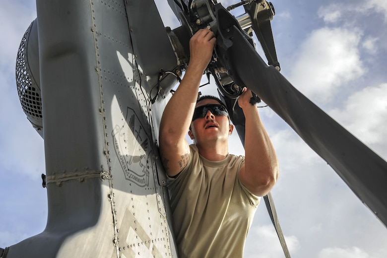Senior Airman Trevor Krutsch, 723d Aircraft Maintenance Squadron hydraulics systems apprentice, unfolds the rotor of an HH-60G Pave Hawk, Dec. 5, 2017, at Moody Air Force Base, Ga. As part of a Phase 1, Phase 2 exercise, the 23d Wing is evaluating its operations, maintenance and logistics to determine its readiness to rapidly deploy. Airmen from the 723d Aircraft Maintenance Squadron folded the main and tail rotor blades inward to make it easier to transport and then unfolded the rotors to practice making the helicopter operational. (U.S. Air Force photo by Airman Eugene Oliver)