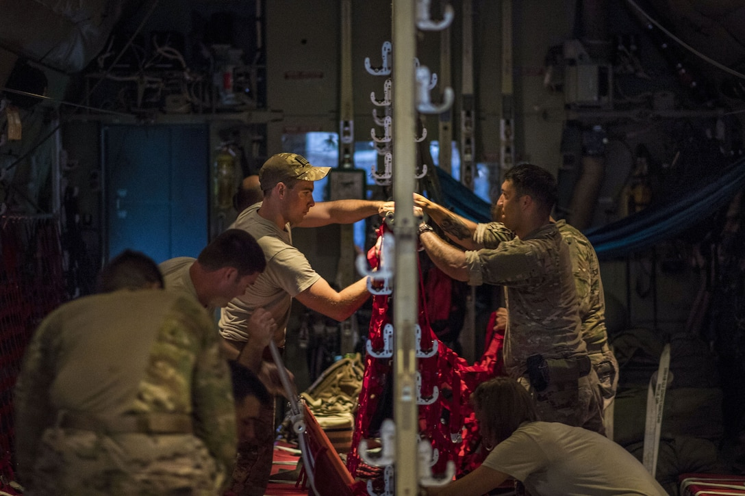 Airmen prepare the interior of a cargo aircraft before a mission.