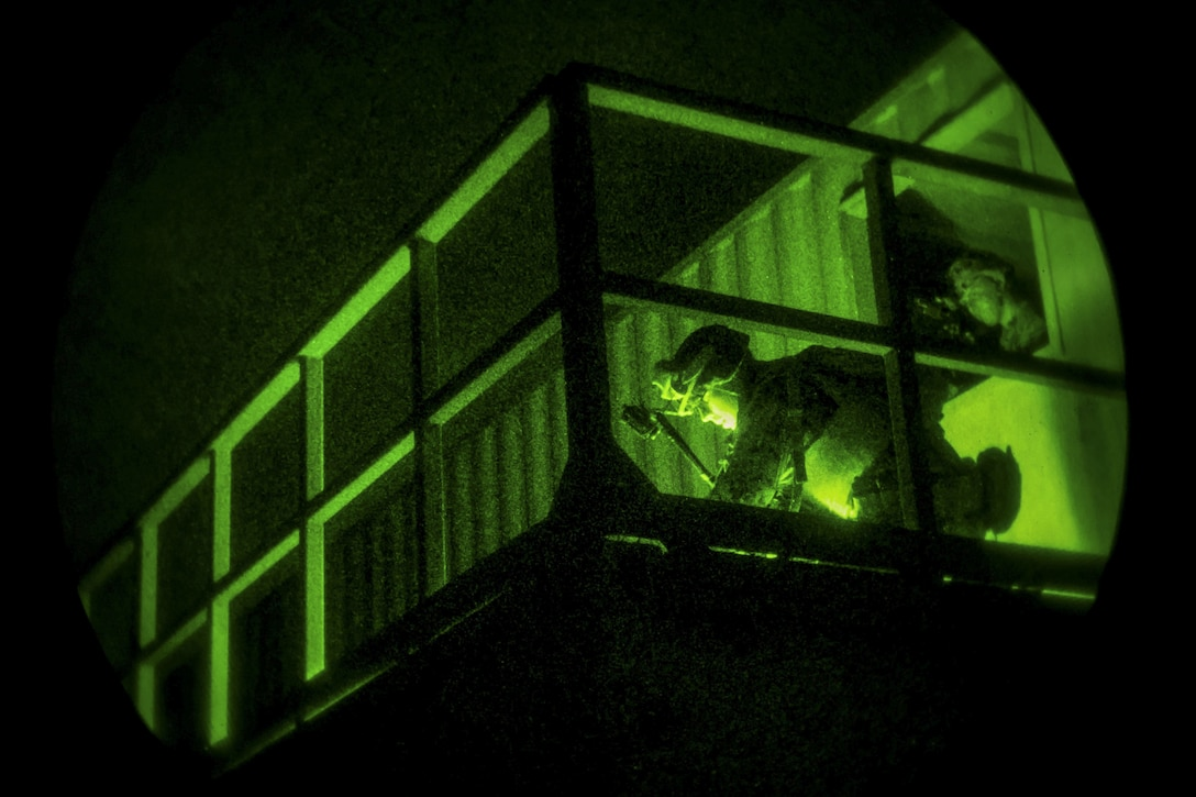 Marines conduct clearing procedures for a building at night during an exercise.