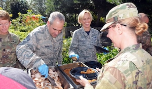 Brig. Gen. Heather Pringle, commander, 502nd Air Base Wing Joint Base San Antonio, and Chief Master Sgt. Kristopher Berg, 502nd ABW and JBSA command chief, help serve a Thanksgiving-style feast to Warrior Transition Battalion Soldiers and their families Nov. 17 at the Warrior and Family Support Center at Joint Base San Antonio-Fort Sam Houston.