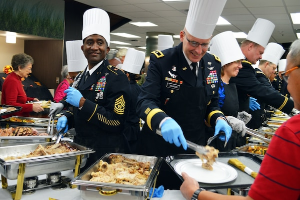 Brooke Army Medical Center commanding general Brig. Gen. Jeffrey Johnson and Command Sgt. Maj. Diamond Hough help serve Thanksgiving dinner to more than 1,000 guests Nov. 23 in the BAMC Dining Room at Joint Base San Antonio-Fort Sam Houston.