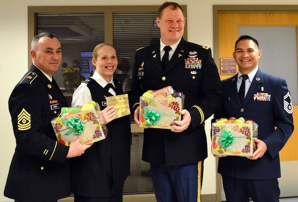 Army Master Sgt. Kenneth Carey, Army Capt. Melissa Kottke, Army Col. Shawn Nessen and Air Force Senior Master Sgt. Ernesto Otero prepare to deliver fruit baskets to inpatients Nov. 23 at Brooke Army Medical Center.