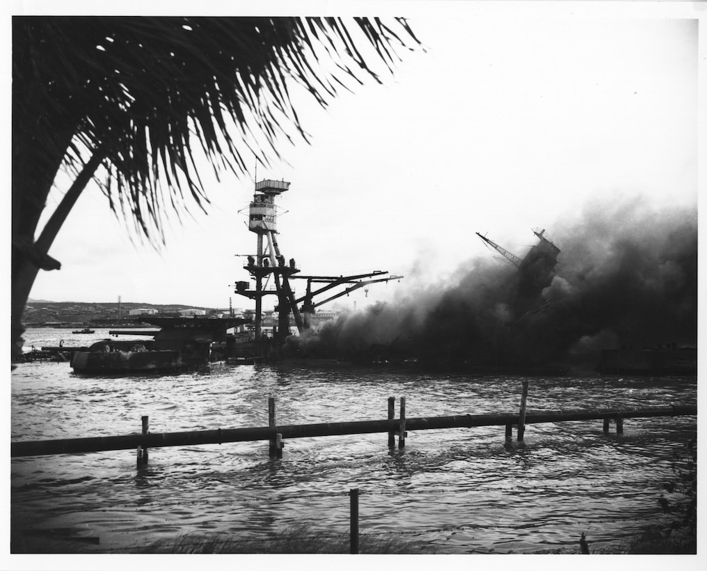 The battleship USS Utah lies capsized and burning as the cruiser USS Raleigh lists in the background at Pearl Harbor, Hawaii, Dec. 7, 1941.