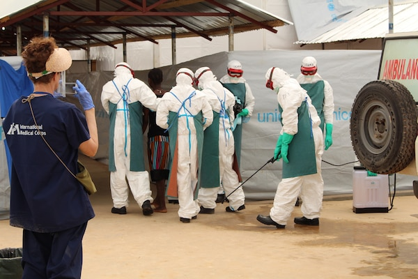 People in white, full-body protective gear walk with a woman into a makeshift entryway.