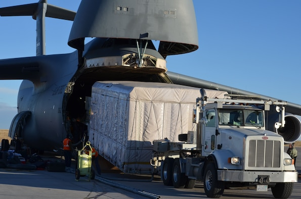 A C-5M Super Galaxy, flown by a Westover Air Reserve Base 337th Airlift Squadron crew, is seen at Buckley Air Force Base, Colo., during loading of a GOES-S weather satellite.