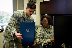 Senior Airman Ramon Santiago-Rosado, 437th Airlift Wing Executive Support Services administrator reviews an award package with Master Sgt. Denise McQueen, 437th AW Executive Support Services superintendent at Joint Base Charleston, S.C., Dec. 4, 2017