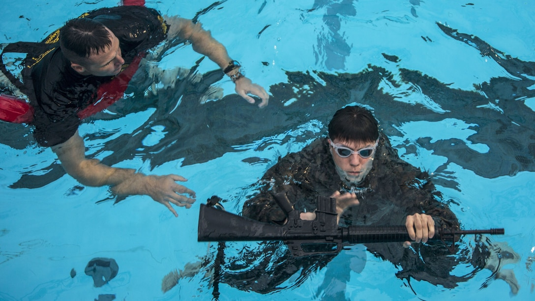 A Marine in a pool observes another Marine treading water while holding a rifle.