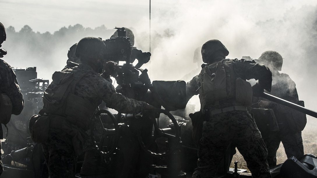 Smoke surrounds a howitzer, as a Marine looks through its sight and others and others work nearby.