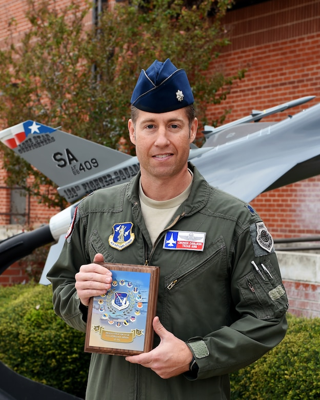Lt. Col. Bryan Carlson, an F-16 Fighting Falcon instructor pilot assigned to the Air National Guard's 149th Fighter Wing, poses with his 2017 High Flyer of the Year award (for F-16 pilots) at Joint Base San Antonio-Lackland, Kelly Field Annex, Texas, Nov. 30, 2017.(Air National Guard photo by Tech. Sgt. Mindy Bloem)